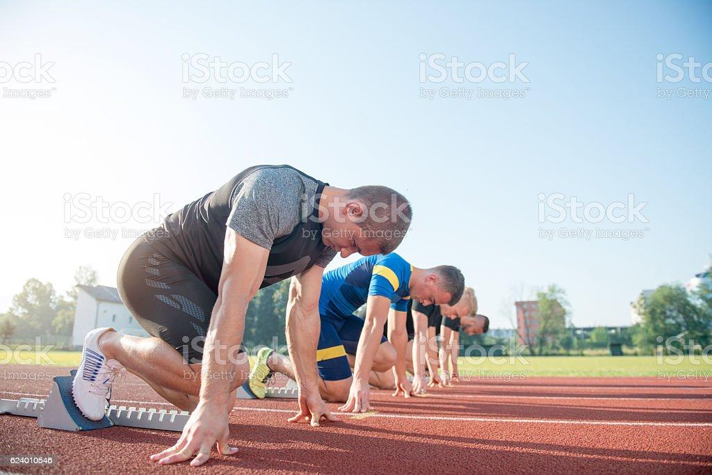 Runners preparing for race at starting blocks stock photo