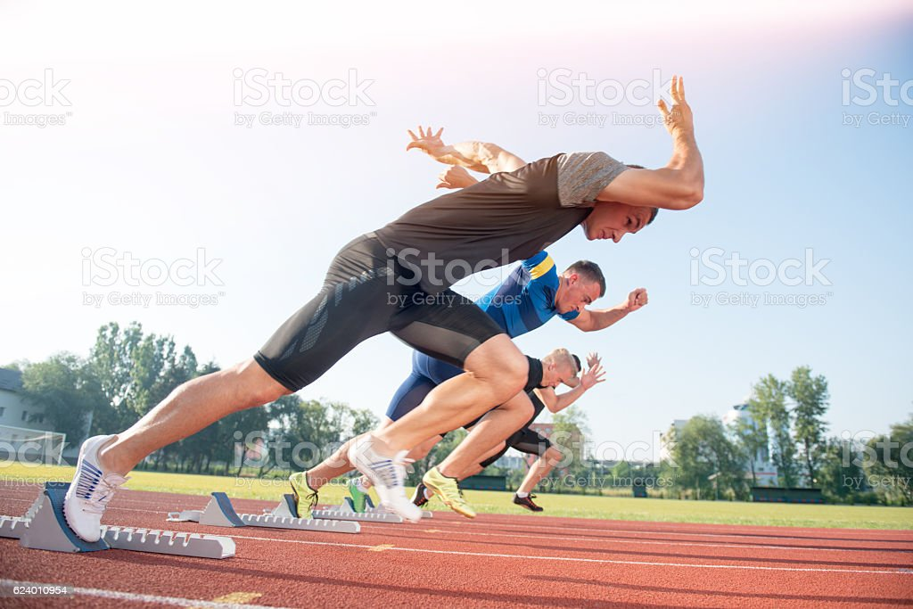 Runners preparing for race at starting blocks stock photo