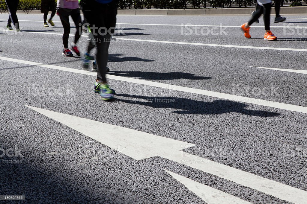 Runners running along the white line stock photo