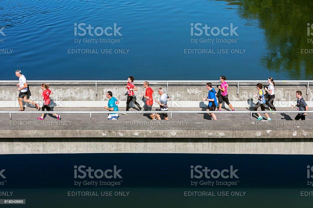 Runners running over the bridge, elevated view stock photo
