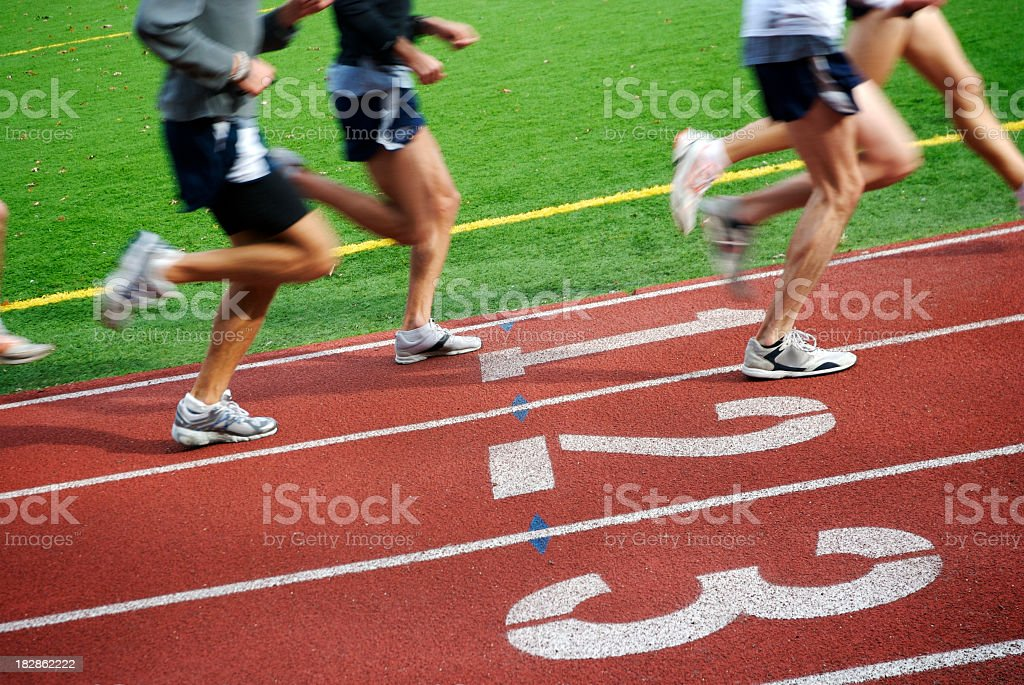 Runners Speed by on Running Track stock photo