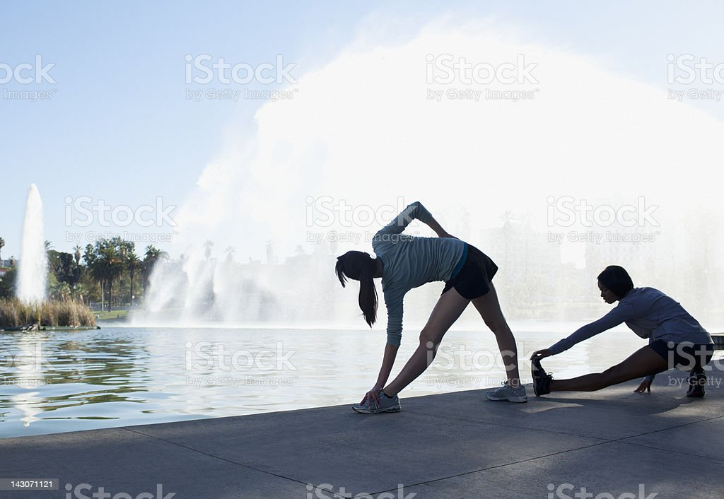Runners stretching by fountain in lake royalty-free stock photo