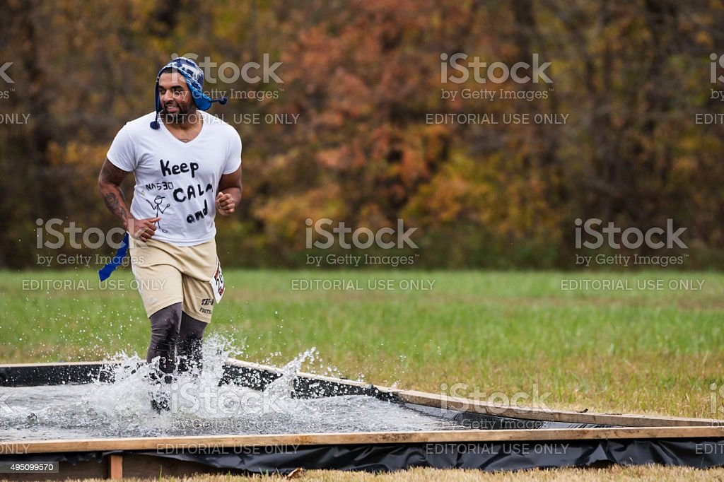 Runners wade through blood pit in Zombie Halloween 5K stock photo