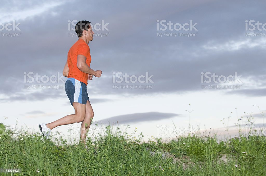 running adult male wearing a orange shirt and blue shorts royalty-free stock photo