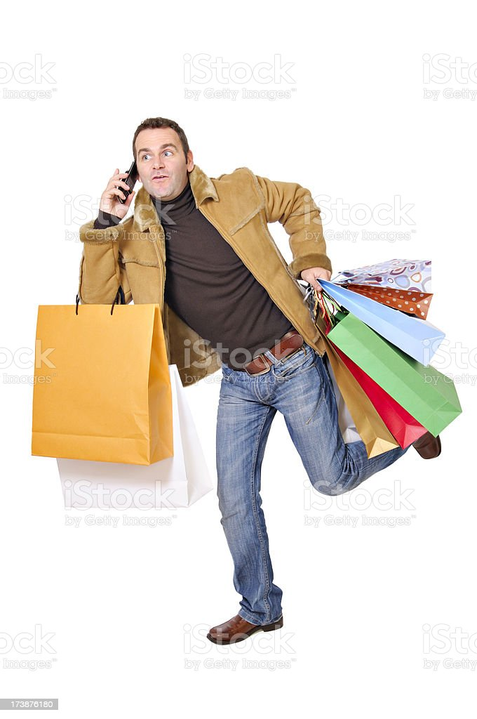 Running and on the phone with shopping bags royalty-free stock photo
