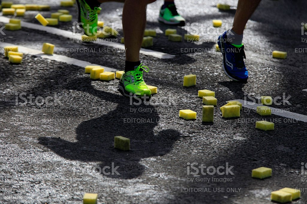 running athletes passing sponges on the road stock photo