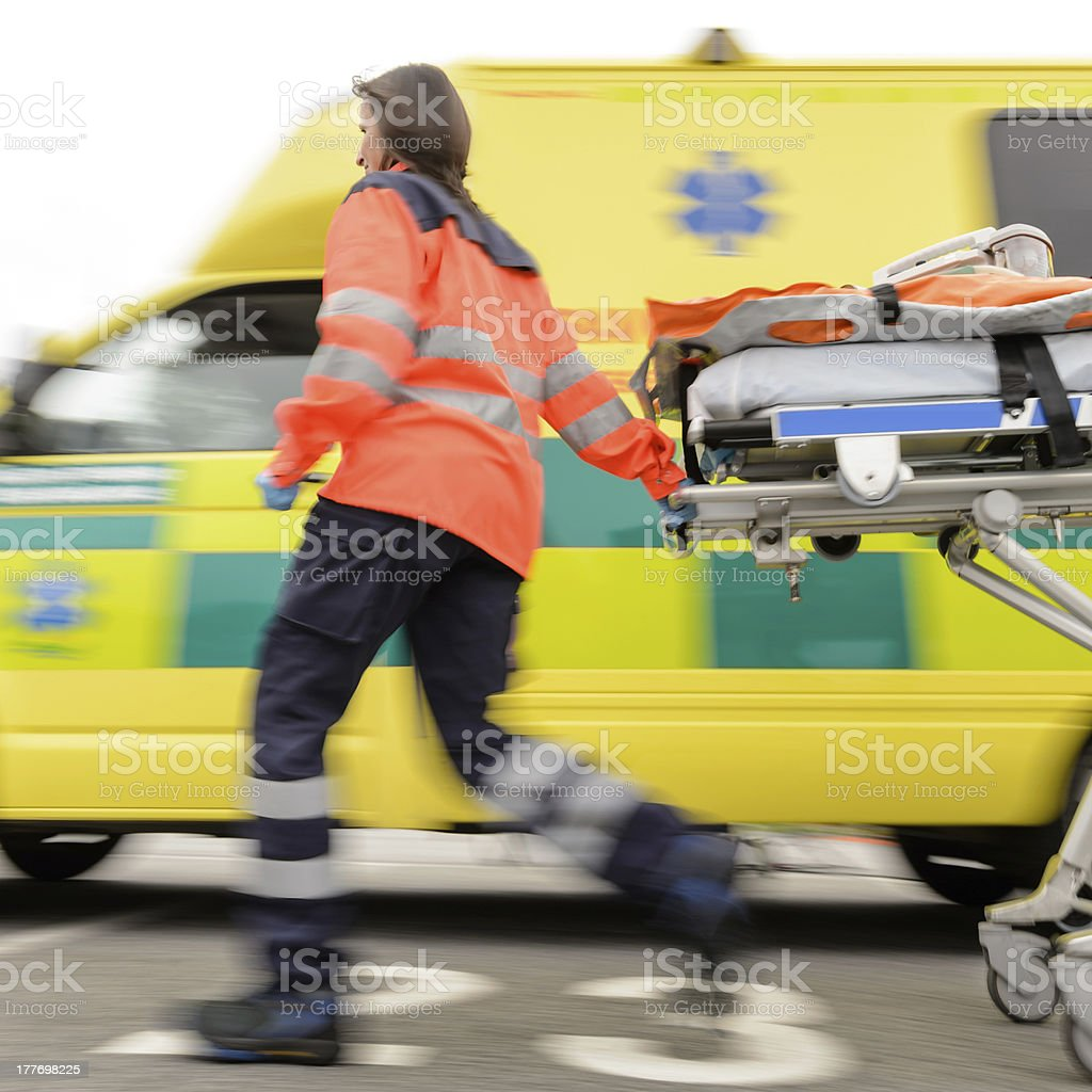 Running blurry paramedic woman pulling gurney stock photo