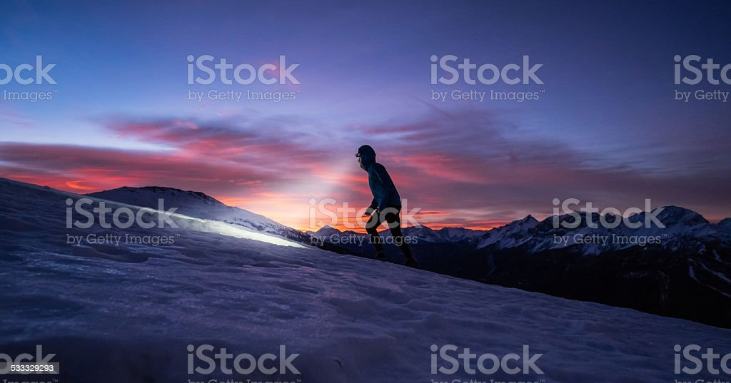 Running by night on the snow on a mountain stock photo