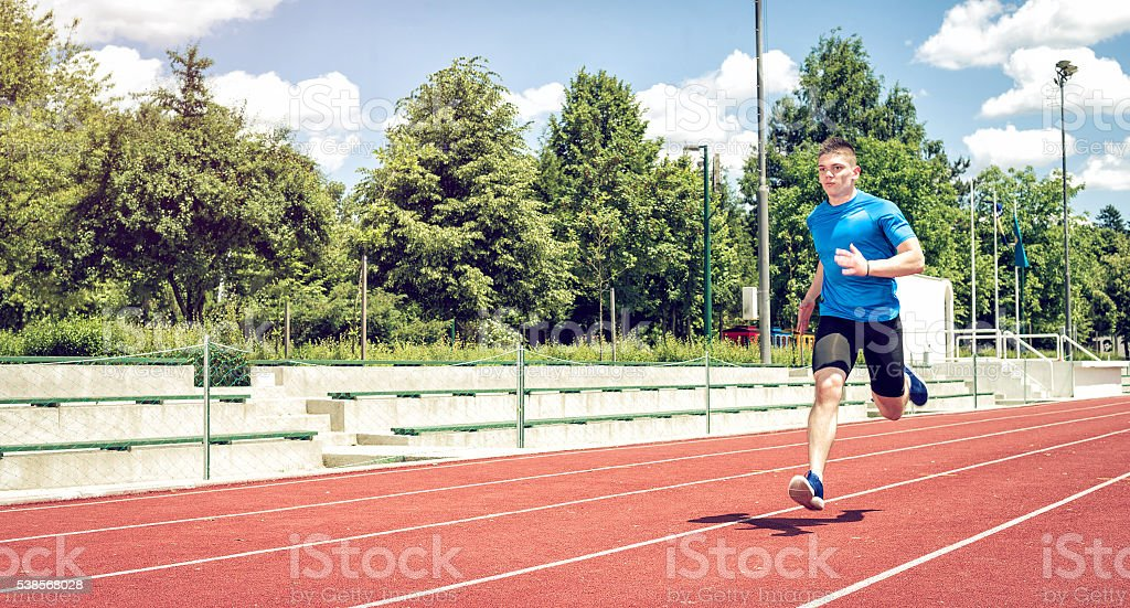 Running fast on athletic field track. stock photo