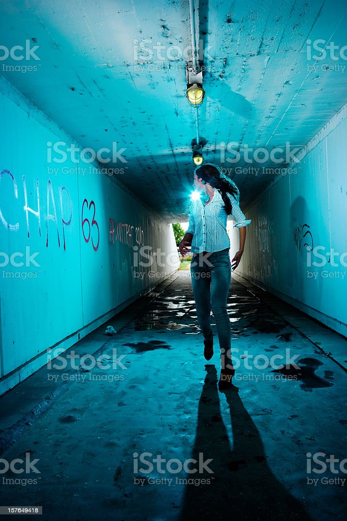 Running girl looking backwards in tunnel stock photo