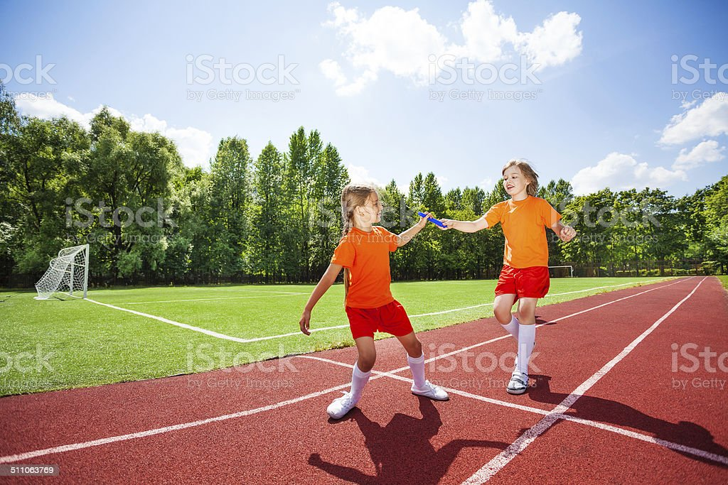Running girl with baton hands it to other runner stock photo