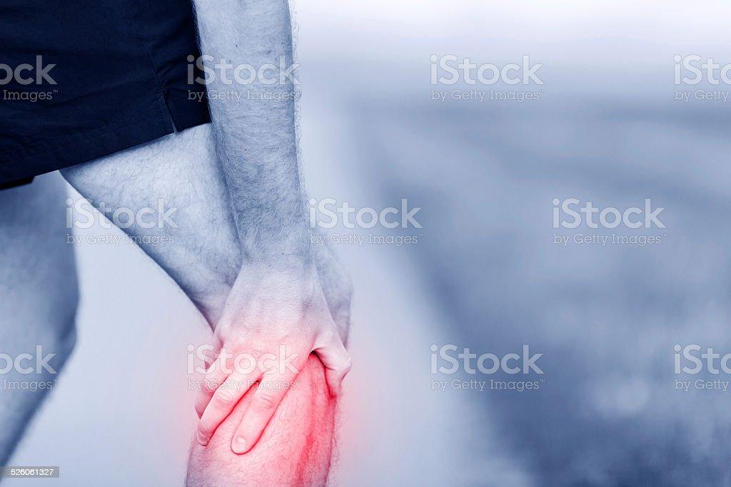 Running injury, calf or knee pain stock photo