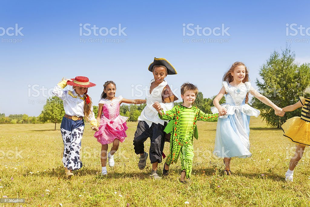 Running kids wearing costumes outside in field stock photo