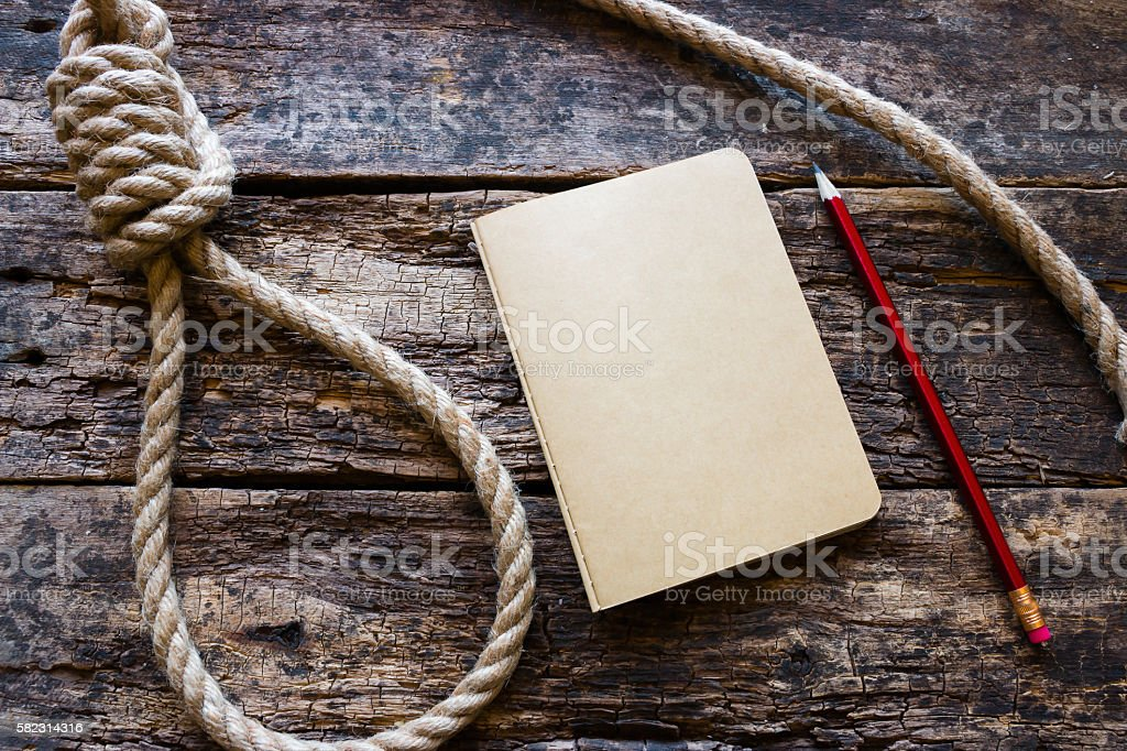 running knot and a suicide note on a wooden background stock photo
