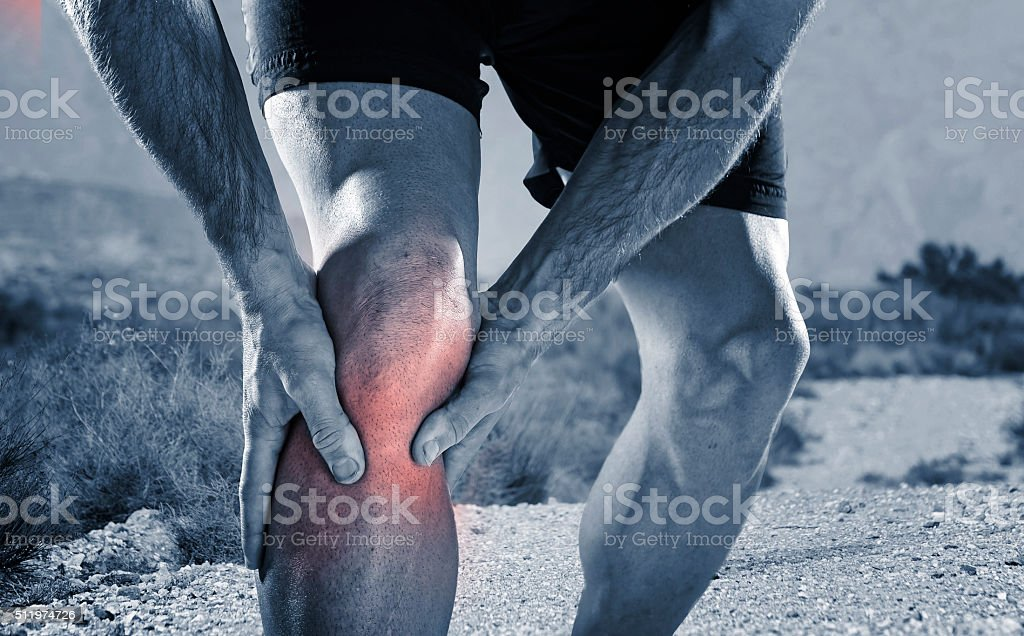 running man holding knee in pain suffering muscle cramp injury stock photo