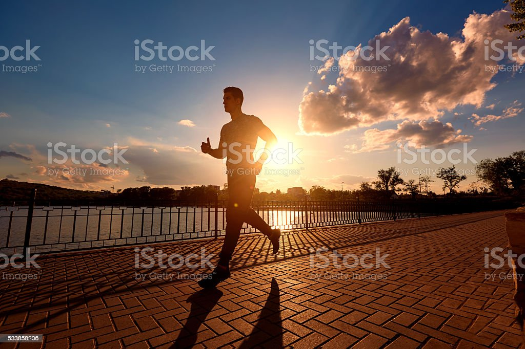 Running man silhouette in sunset time. stock photo