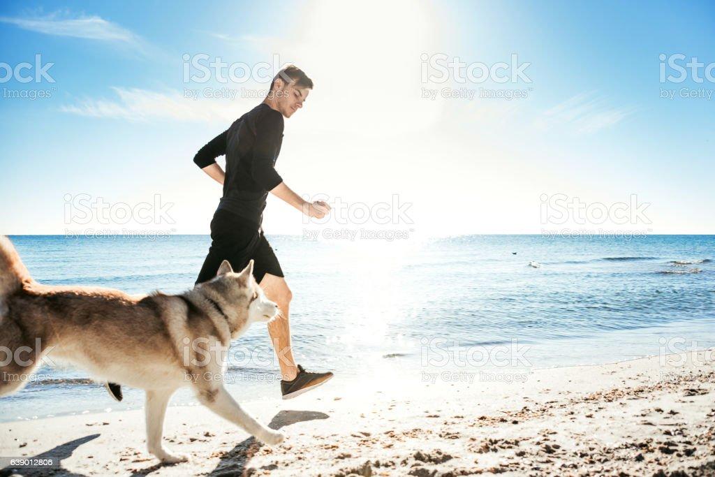 Running man with husky dog stock photo