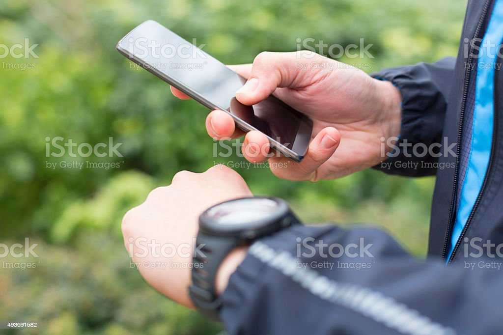 Running man with Mobile phone connected to a smart watch stock photo