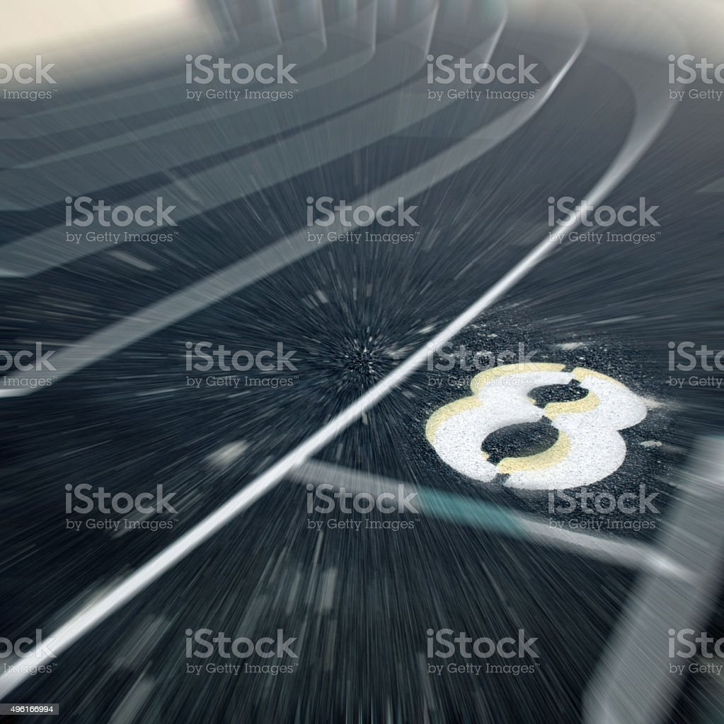 Running  number eight on a track and field lane stock photo