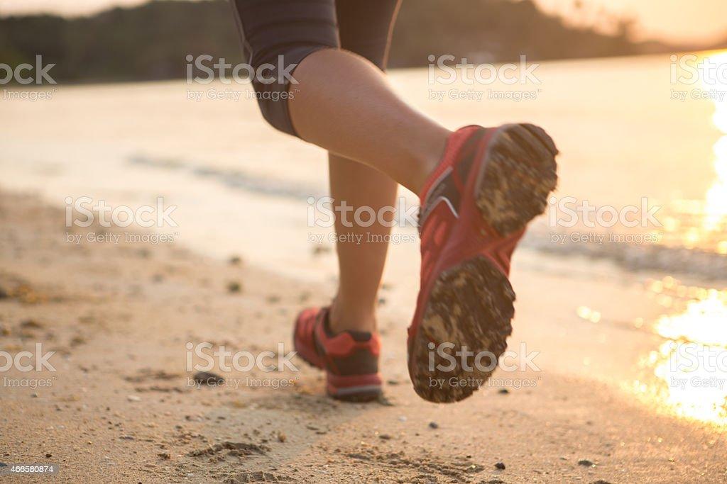 Running on the beach at sunset stock photo