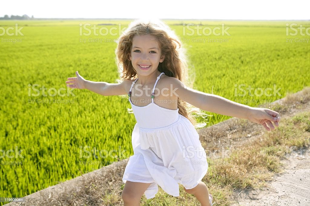 running open arms little happy girl in meadow track royalty-free stock photo