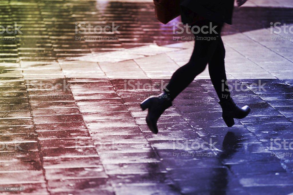 Running pedestrians on rain wet square royalty-free stock photo