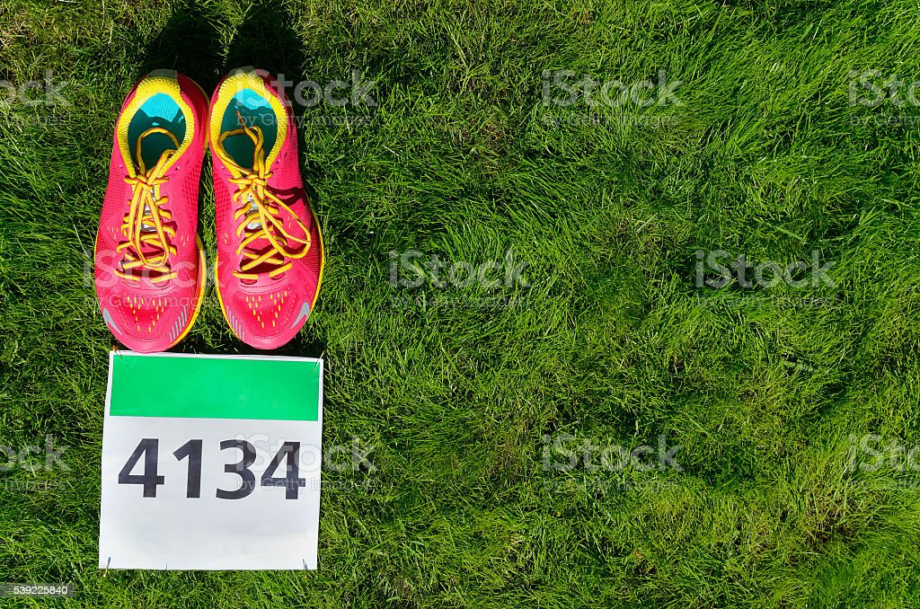 Running shoes and marathon race bib (number) on grass stock photo