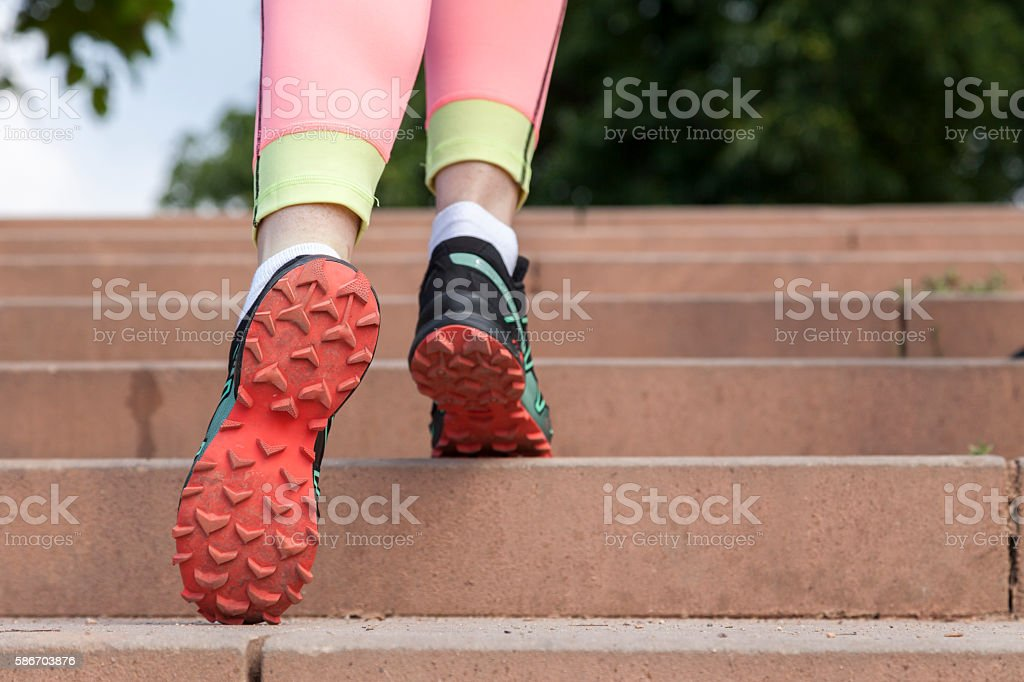 running shoes while running up the stairs stock photo