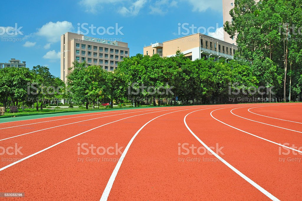 Running track with lanes over trees and clouds. stock photo