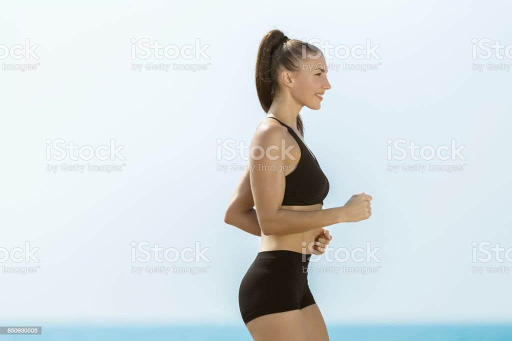 Running woman at the beach stock photo