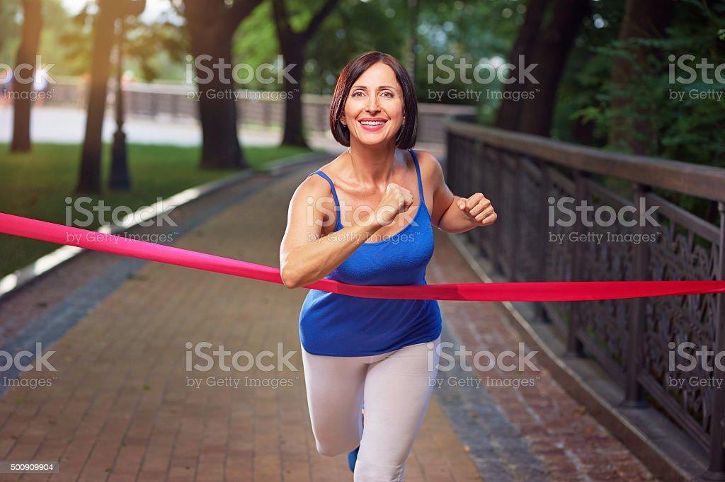running woman crosses finish line stock photo