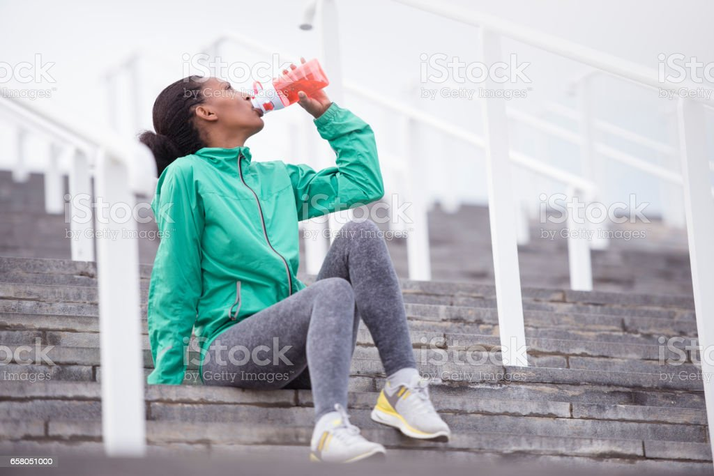 Running woman drinking a mineral water, sitting on stairs. stock photo