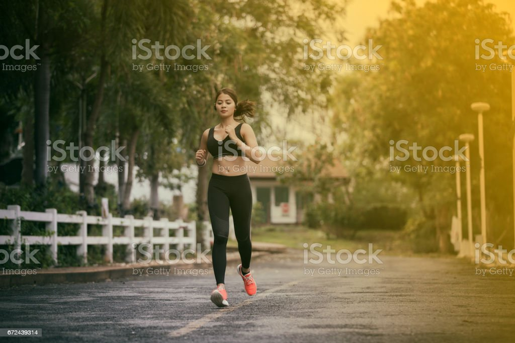 Running woman. Female runner jogging during outdoor  on road .Young mixed race girl jogging stock photo