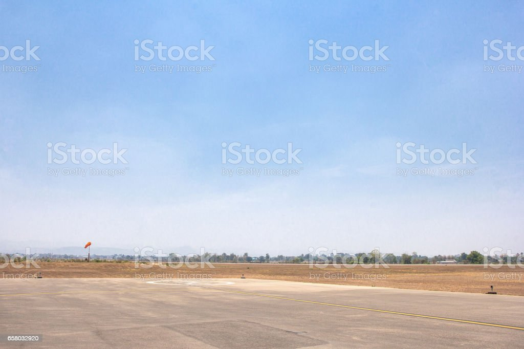 Runway of small airport shot against a backdrop of blue sky stock photo