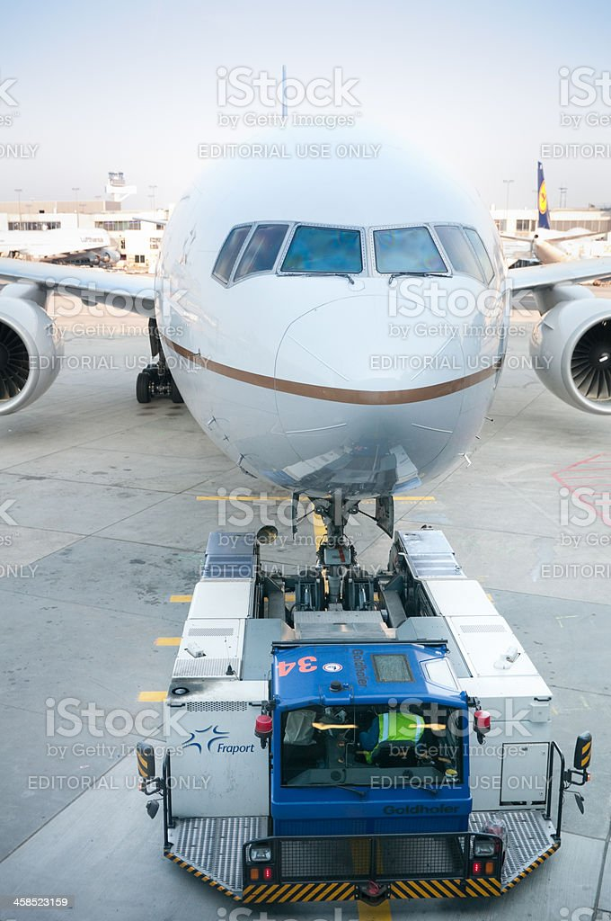 Runway tractor pushing Boeing 777-200 aircraft at Frankfurt Airport royalty-free stock photo