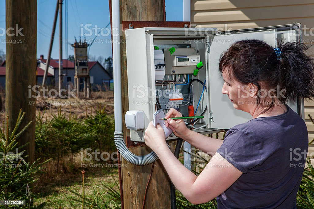 Rural adult women to take readings of electricity meter outdoors stock photo