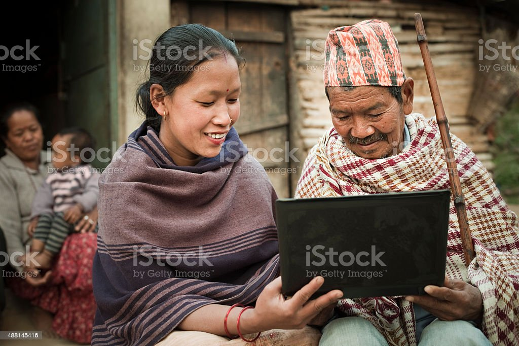 Rural Asian young woman showing laptop to a senior man. stock photo