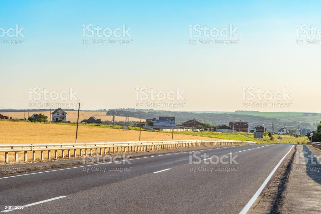 Rural asphalt road with markings and guard rail. Belgorod region, Russia. stock photo