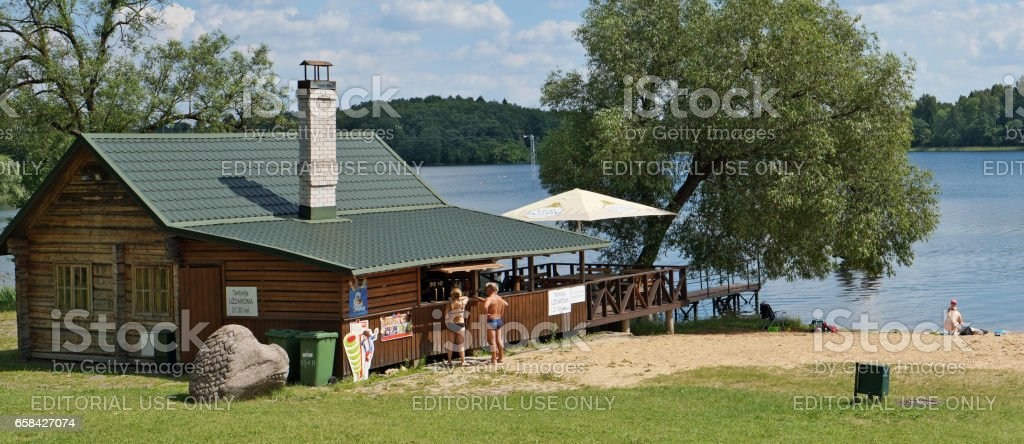 VILNIUS, LITHUANIA - JUNE 15, 2016: Rural bath and beer pub on the sandy beach of the Vilnoja (Waves) lake in the World Stones Park. The sculptor of Vidmantas Martikonis has created this Stone Park in 2001 stock photo
