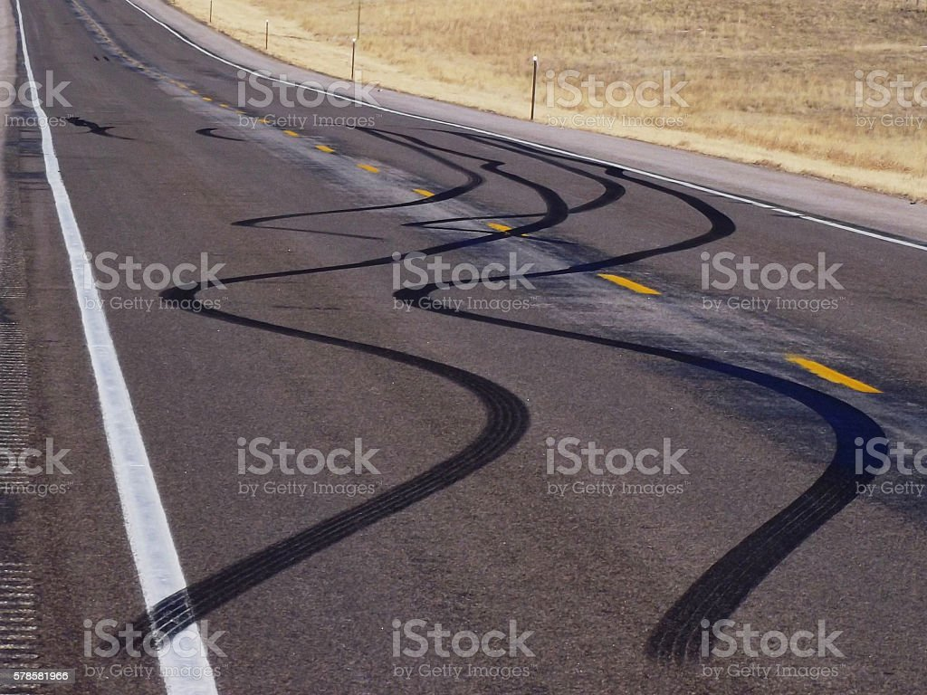 Rural Blacktop Highway with Squiggly Black Tire Tracks stock photo