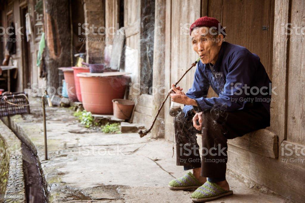 Rural China Old Senior Chinese Man Smoking Pipe at his Village Home stock photo
