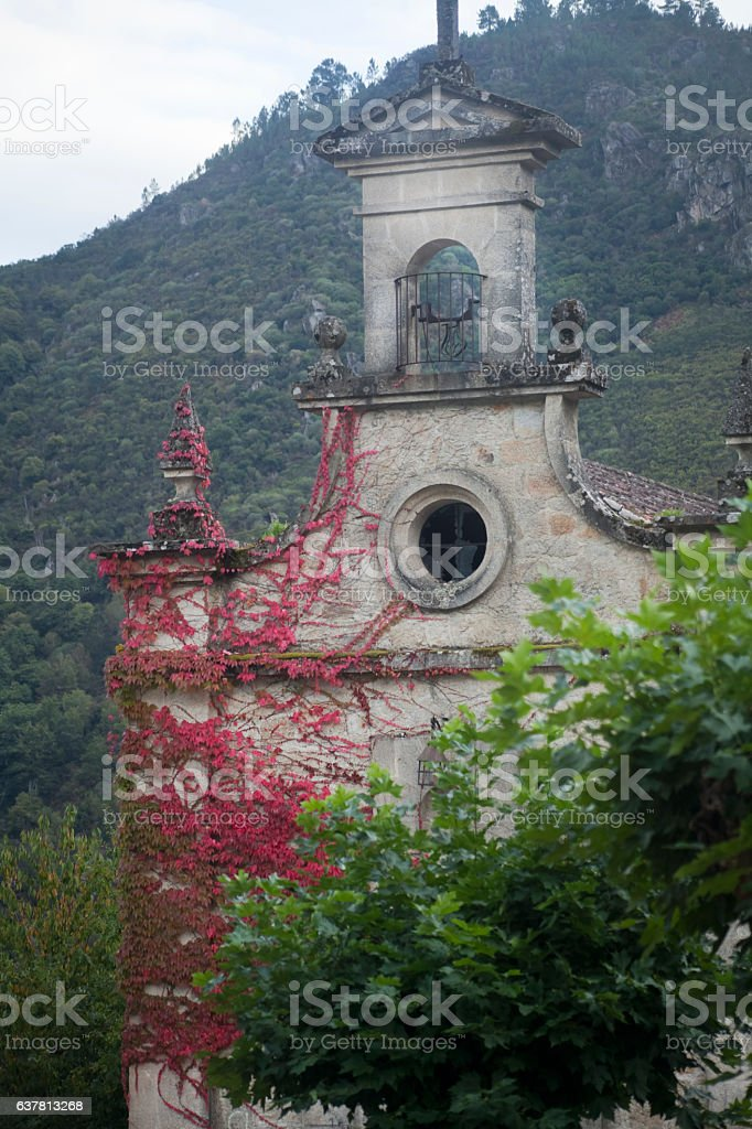 Rural church facade, red ivy leaves in Galicia, Spain. stock photo