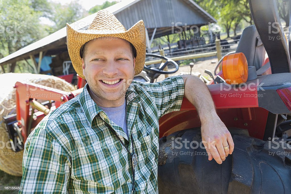 Rural farm worker leaning on tractor royalty-free stock photo