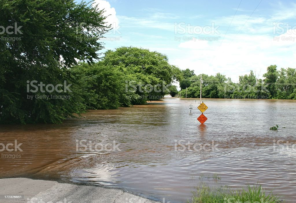 Rural Flooded Road with signs and trees royalty-free stock photo