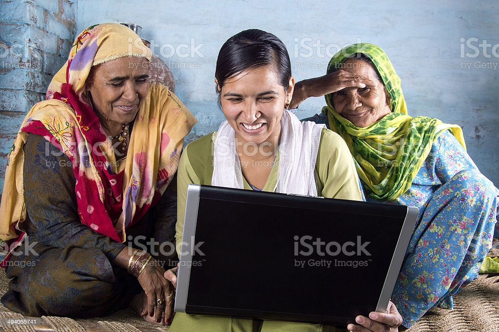 Rural Girl Holding Laptop with Seniors stock photo