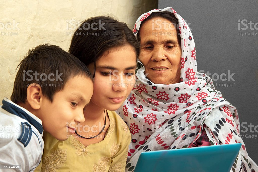 Rural Indian women using laptop with her younger daughter royalty-free stock photo