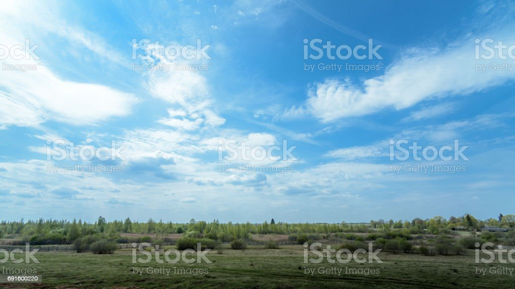 rural panorama of field at the pens on a background of blue sky stock photo
