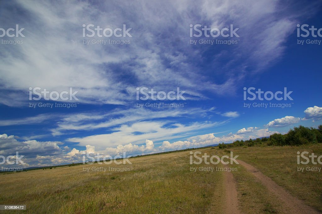 Rural road and clouds stock photo