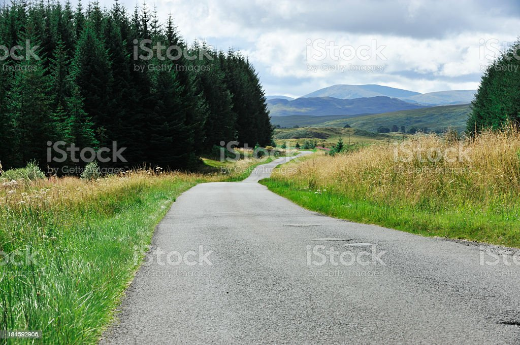 Rural road in remote Scottish countryside with woodland stock photo