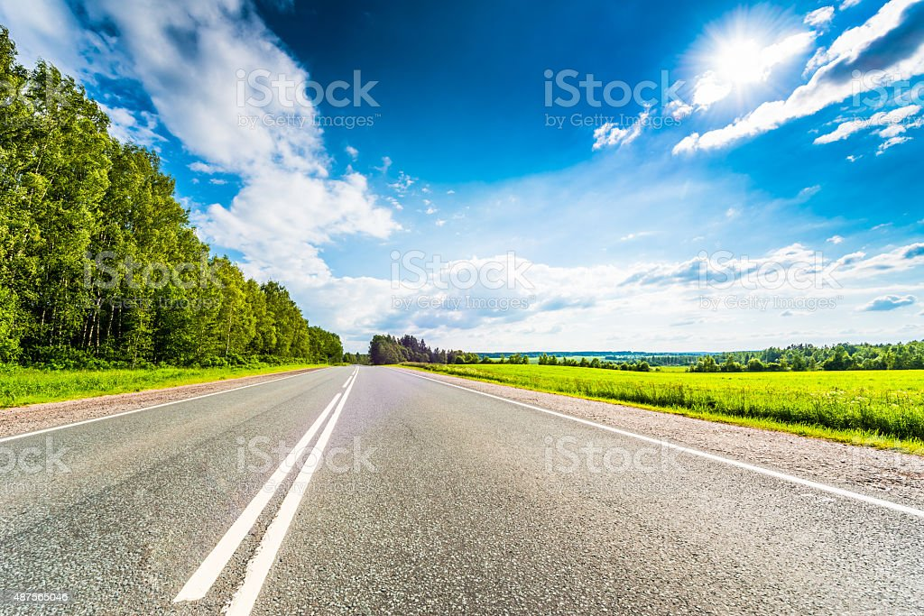 Rural road passing through fields and woods stock photo